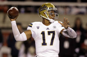 Photo - UCLA quarterback Brett Hundley (17) passes the ball against Utah in the first quarter during an NCAA college football game on Thursday, Oct. 3, 2013, in Salt Lake City. (AP Photo/Rick Bowmer)