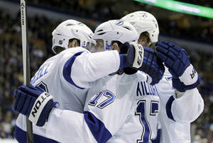 Photo - Tampa Bay Lightning's Alex Killorn (17) is congratulated by teammates after scoring a goal during the first period of an NHL hockey game against the St. Louis Blues, Tuesday, March 4, 2014 in St. Louis.(AP Photo/Tom Gannam)