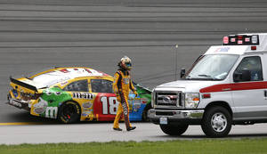 Photo - Driver Kyle Busch (18) walks to an ambulance past his wrecked race car during a NASCAR Sprint Cup series auto race at Kansas Speedway in Kansas City, Kan., Sunday, Oct. 6, 2013. (AP Photo/Orlin Wagner)