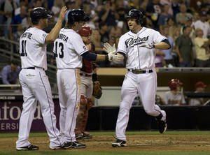 photo -   San Diego Padres' Chase Headley, right, is greeted at the plate by teammates Logan Forsythe, left, and Chris Denorfia,second from left, after driving them in on his three-run home run against the Arizona Diamondbacks in the third inning of their baseball game Friday, Sept. 7, 2012, in San Diego. Diamondbacks catcher Miguel Montero watches behind. (AP Photo/Gregory Bull)