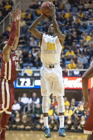 Photo - West Virginia's Eron Harris, right, shoots a 3-point basket over Oklahoma's Jordan Woodard during the second half of an NCAA college basketball game on Wednesday, Feb. 5, 2014, in Morgantown, W.Va. West Virginia won 91-86 in overtime. (AP Photo/Andrew Ferguson)