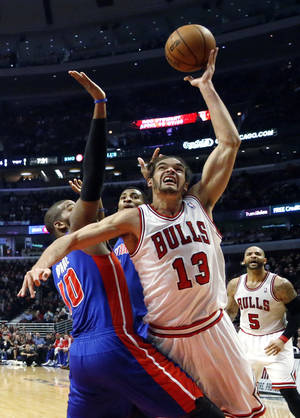 Photo - Chicago Bulls center Joakim Noah (13) shoots over Detroit Pistons center Greg Monroe (10) during the first half of an NBA basketball game, Wednesday, Jan. 23, 2013, in Chicago. (AP Photo/Charles Rex Arbogast)