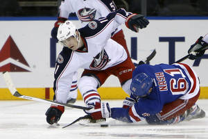 Photo - New York Rangers' Rick Nash (61) collides with Columbus Blue Jackets' Matt Calvert (11) as they battle for possession during the first period of an NHL hockey game Thursday, Dec. 12, 2013, in New York. (AP Photo/Jason DeCrow)