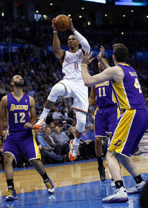Photo - Oklahoma City Thunder's Russell Westbrook (0) scores in the first half of an NBA basketball game where the Oklahoma City Thunder play the Los Angeles Lakers at the Chesapeake Energy Arena in Oklahoma City, on March 13, 2014.  Photo by Steve Sisney The Oklahoman