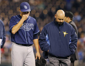 Photo - Tampa Bay Rays starting pitcher Matt Moore, left, walks off the field with a trainer following an injury during the sixth inning of the MLB American League baseball game against the Kansas City Royals at Kauffman Stadium in Kansas City, Mo., Monday, April 7, 2014. (AP Photo/Orlin Wagner)