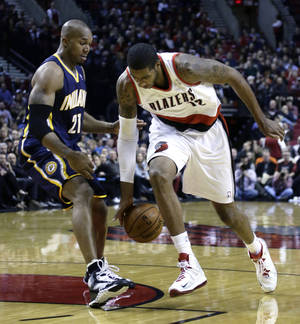 Photo - Portland Trail Blazers forward LaMarcus Aldridge, right, loses his handle on the ball as he drives to the basket against Indiana Pacers forward David West during the first half of an NBA basketball game in Portland, Ore., Monday, Dec. 2, 2013. (AP Photo/Don Ryan)
