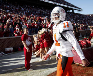 Photo - OSU's  Zac  Robinson walks off the field after the Bedlam college football game between the University of Oklahoma Sooners (OU) and the Oklahoma State University Cowboys (OSU) at the Gaylord Family-Oklahoma Memorial Stadium on Saturday, Nov. 28, 2009, in Norman, Okla. Photo by Bryan Terry, The Oklahoman