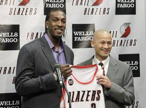 Photo - Portland Trail Blazers' Gerald Wallace, left, smiles as he is introduced by Trail Blazers general manager Rich Cho during a interview before the start of NBA basketball game with the Denver Nuggets Friday, Feb. 25, 2011, in Portland, Ore. Gerald Wallace was acquired from Charlotte in exchange for veteran center Joel Przybilla, second-year forward Dante Cunningham and journeyman center Sean Marks. (AP Photo/Rick Bowmer) <strong>Rick Bowmer</strong>