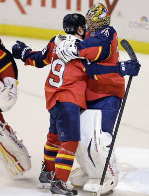 Photo - Florida Panthers' Scottie Upshall (19) and goalie Jacob Markstrom (35) celebrate after defeating the New York Rangers 3-2 in an NHL hockey game in Sunrise, Fla., Tuesday, April 23, 2013. (AP Photo/J Pat Carter)