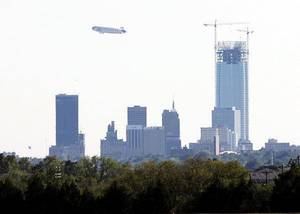Photo - The Farmers Airship, the world's largest airship and one of only two zeppelins in the world passes south of downtown Oklahoma City Monday, September 19, 2011 . Photo by Doug Hoke, The Oklahoman. ORG XMIT: KOD