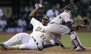 Photo -   Oakland Athletics' Chris Carter, left, slides to score past Cleveland Indians catcher Carlos Santana in the sixth inning of a baseball game Saturday, Aug. 18, 2012, in Oakland, Calif. Carter scored on a single by George Kottaras. (AP Photo/Ben Margot)