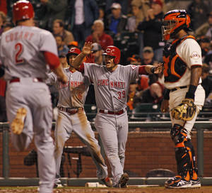 Photo - Cincinnati Reds' Devin Mesoraco (39), center, reacts as Zack Cozart (2) runs toward the plate during the eleventh inning of a baseball game, Saturday, June 28, 2014, in San Francisco.  Mesoraco and Cozart scored on a Chris Heisey triple. Giants catcher Hector Sanchez is at right, and Reds. Billy Hamilton (6) is in the background. (AP Photo/George Nikitin)