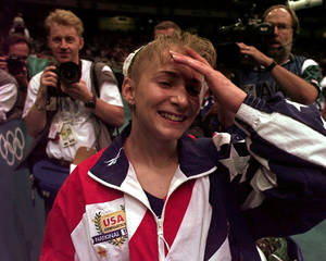 Photo - Members of the media pursue USA's Shannon Miller, of Edmond, Ohio, after the US women's national gymnastics team won the gold in the team competition at the 1996 Centennial Summer Olympics Games in Atlanta on Tuesday, July 23, 1996.  (AP Photo/Amy Sancetta)
