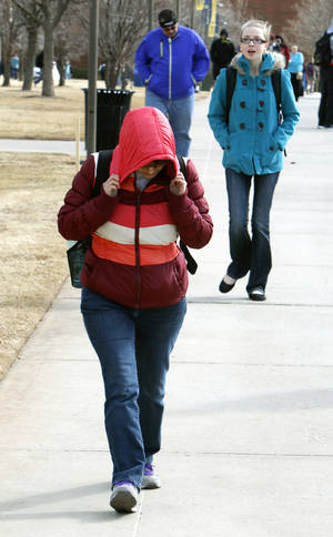 Photo -      A student braces against a powerful wind Thursday as she crosses the campus of the University of Central Oklahoma in Edmond. Photo by Paul Hellstern, The Oklahoman  <strong>PAUL HELLSTERN -   </strong>