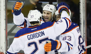 Photo - Edmonton Oilers' Ryan Smyth, center, celebrates his goal with teammates Boyd Gordon, left, and Ales Hemsky, of Czech Republic, during the first period of an NHL hockey game in Calgary, Alberta, Friday, Dec. 27, 2013. (AP Photo/The Canadian Press, Jeff McIntosh)