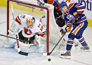 Photo - Calgary Flames goalie Joey MacDonald (35) makes the save on Edmonton Oilers Ales Hemsky (83) during second period NHL hockey action in Edmonton, Alberta, on Monday April 1, 2013. (AP Photo/The Canadian Press, Jason Franson).