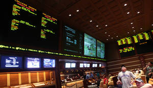 Photo -   FILE - Sports bettors watch the screens in the race and sports book at Wynn Las Vegas, in this March 15, 2009 file photo taken in Las Vegas. Las Vegas casinos think this weekend's NFL week three 2012 games will be the highest-scoring ever _ and that you can thank the league's replacement officials. Oddmakers say casinos are changing their expectations as interim referees add new variables to the game, changing its pace and approaches from players and coaches. (AP Photo/Isaac Brekken)