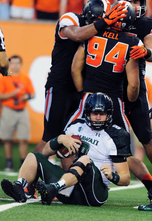 Photo - Hawaii quarterback Taylor Graham (8) sits on the turf after he was sacked by Oregon State defensive end Devon Kell (94) in the third quarter of an NCAA college football game in Corvallis, Ore., Saturday, Sept. 7, 2013. AP Photo/Steve Dykes)
