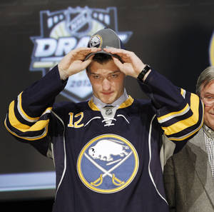 Photo -   Mikhail Grigorenko, a center from Russia, pulls on a Buffalo Sabres cap after being chosen 12th overall in the first round of the NHL hockey draft on Friday, June 22, 2012, in Pittsburgh. (AP Photo/Keith Srakocic)