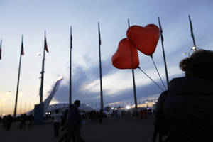 Photo - The Olympic flame burns in the background as a visitor walks through the Olympic Park with heart shaped balloons in celebration of Valentine's Day at the 2014 Winter Olympics, Friday, Feb. 14, 2014, in Sochi, Russia. (AP Photo/David Goldman)