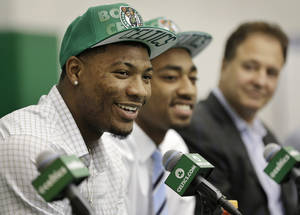 Photo - Boston Celtics 2014 NBA basketball draft picks Marcus Smart, left, and James Young, center, face reporters as Celtics co-owner Stephen Pagliuca, right, looks on during a news conference held to introduce the players, Monday, June 30, 2014, in Waltham, Mass. (AP Photo/Steven Senne)