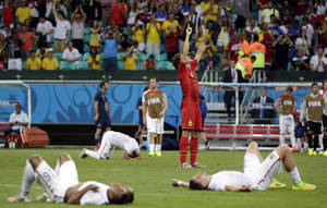 Photo - Exhausted US players lie on the ground as Belgium's Axel Witsel (6) celebrates at the end of the extra time during the World Cup round of 16 soccer match between Belgium and the USA at the Arena Fonte Nova in Salvador, Brazil, Tuesday, July 1, 2014. Belgium held on to beat US 2-1 in extra time.(AP Photo/Felipe Dana)