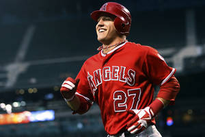 photo -   FILE - In this Aug. 31, 2012, file photo, Los Angeles Angels' Mike Trout smiles after scoring against the Seattle Mariners during a baseball game in Seattle. Trout unanimously won the American League Rookie of the Year Monday, Nov. 12. (AP Photo/Elaine Thompson, File)