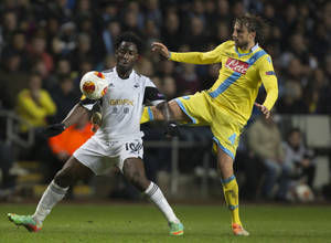 Photo - Swansea's Wilfried Bony, left, fights for the ball against Napoli's Henrique during their Europa League round of 32 first leg soccer match at the Liberty Stadium, Swansea, Wales, Thursday Feb. 20, 2014. (AP Photo/Jon Super)