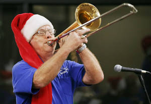 Photo - Rich Rasmussen plays the trombone with the Flying High Tinker Air Force Base Band during the holiday lighting ceremony at Rose State College.