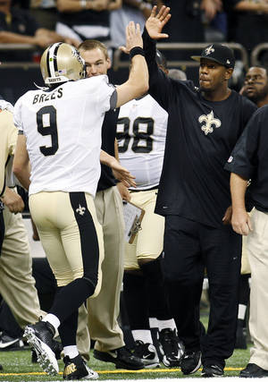Photo -   New Orleans Saints linebacker Jonathan Vilma, right, greets quarterback Drew Brees (9) after Brees' touchdown pass in the first half of an NFL football game against the Washington Redskins in New Orleans, Sunday, Sept. 9, 2012. (AP Photo/Bill Haber)