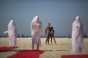 Photo - Beachgoers look at a trio of veiled wrapped mannequins that are part of a a protest staged by Rio de Paz activists on Copacabana beach to press for clarifications on missing persons including a bricklayer who recently disappeared, in Rio de Janeiro, Brazil, Wednesday, July 31, 2013. The 42-year-old father of six was picked up for police questioning on suspicions of involvement in drug trafficking, but was released shortly thereafter. He has not been seen from since. The Rio de Paz civic organization cites official statistics showing that nearly 35,000 people were reported as missing in Rio state alone over the past five years. (AP Photo/Felipe Dana)
