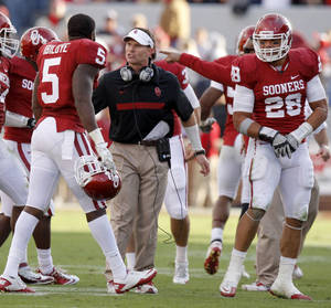 Photo - Oklahoma defensive coordinator Brent Venables talks with Oklahoma's Joseph Ibiloye (5) and Travis Lewis (28) during the college football game between the Texas A&M Aggies and the University of Oklahoma Sooners (OU) at Gaylord Family-Oklahoma Memorial Stadium on Saturday, Nov. 5, 2011, in Norman, Okla. Photo by Bryan Terry, The Oklahoman ORG XMIT: KOD