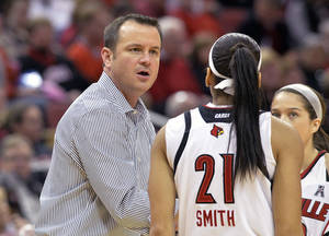Photo - Louisville head coach Jeff Walz, left, talks with Bria Smith during the first half of an NCAA basketball game against Memphis Sunday, Jan. 26, 2014 in Louisville, Ky. (AP Photo/Timothy D. Easley)