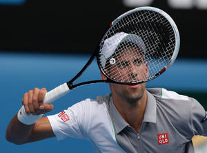Photo - Novak Djokovic of Serbia makes a forehand return to Leonardo Mayer of Argentina during their second round match at the Australian Open tennis championship in Melbourne, Australia, Wednesday, Jan. 15, 2014.(AP Photo/Aaron Favila)