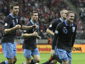 Photo -   England's Wayne Rooney ,right, celebrates his goal against Poland during their World Cup Group H qualifying soccer match at National Stadium in Warsaw, Poland, Wednesday, Oct. 17, 2012 (AP Photo/Czarek Sokolowski