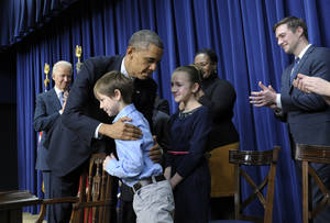Photo - President Barack Obama, accompanied by Vice President Joe Biden, left, hugs eight-year-old letter writer Grant Fritz during a news conference on proposals to reduce gun violence, Wednesday, Jan. 16, 2013, in the South Court Auditorium at the White House in Washington. Obama and Biden were joined by law enforcement officials, lawmakers and children who wrote the president about gun violence following the shooting at an elementary school in Newtown, Conn., last month. (AP Photo/Susan Walsh)