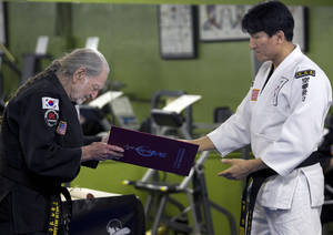 Photo - Willie Nelson, the country music icon who turns 81 this week, bows as he receives his fifth-degree black belt in the martial art of Gong Kwon Yu Sul on Monday, April 28, 2014, in Austin, Texas.  (AP Photo/Austin American-Statesman, Ralph Barrera)  AUSTIN CHRONICLE OUT, COMMUNITY IMPACT OUT, INTERNET AND TV MUST CREDIT PHOTOGRAPHER AND STATESMAN.COM, MAGS OUT