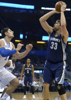 Photo - Memphis Grizzlies center Marc Gasol (33) goes up for a shot in front of Orlando Magic center Nikola Vucevic during the first half of an NBA basketball game in Orlando, Fla., Wednesday, Feb. 12, 2014. (AP Photo/Phelan M. Ebenhack)