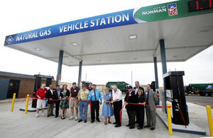 Photo - Norman Mayor Cindy Rosenthal, center, cuts the ribbon Friday to mark the grand opening of the city's  compressed natural gas fueling station. PHOTO BY PAUL B. SOUTHERLAND, THE OKLAHOMAN