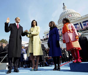 photo - FILE - In this Jan. 20, 2009, file photo, Barack Obama, left, takes the oath of office from Chief Justice John Roberts, not seen, as his wife Michelle, holds the Lincoln Bible and daughters Sasha, right and Malia, watch at the U.S. Capitol in Washington. Obama's second inauguration is shaping up as a high-energy celebration smaller than his first milestone swearing-in, yet still designed to mark his unprecedented role in American history with plenty of eye-catching glamour. A long list of celebrity performers will give the once-every-four years right of democratic passage the air of a star-studded concert, from the bunting-draped Capitol's west front of the Capitol, where Obama takes the oath Jan. 21, to the Washington Convention Center, which is expected to be packed with 40,000 ball-goers that evening. (AP Photo/Chuck Kennedy, Pool)