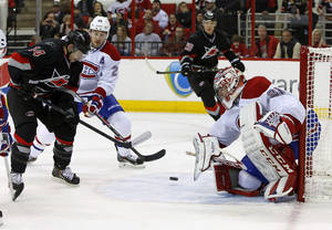 Photo - Carolina Hurricanes' Nathan Gerbe (14) tries to gather in the puck in front of Montreal Canadiens goalie Carey Price (31) as Canadiens' Josh Gorges (26) joins the play during the second period of an NHL hockey game in Raleigh, N.C., Tuesday, Dec. 31, 2013. (AP Photo/Karl B DeBlaker)