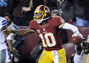Photo - Washington Redskins quarterback Robert Griffin III (10) celebrates his touchdown during the second half of an NFL football game against the Dallas Cowboys on Sunday, Dec. 30, 2012, in Landover, Md. (AP Photo/Nick Wass)