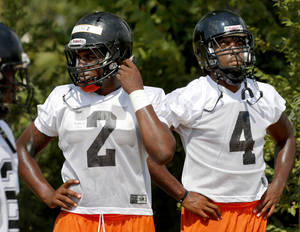 photo - Deondre Clark, left, and D.J. Ward of Douglass wait in line during football practice at Douglass high school in Oklahoma City, Tuesday, August 7, 2012. Photo by Bryan Terry, The Oklahoman