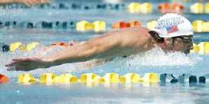 Photo - Michael Phelps competes in the 100-meter butterfly during the Arena Grand Prix swim meet, Thursday, April 24, 2014, in Mesa, Ariz. It is Phelps' first competitive event after a nearly two-year retirement. (AP Photo/Matt York)