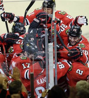 Photo - Chicago Blackhawks' Patrick Kane (88) celebrates with teammates after scoring the game-winning goal during overtime period in Game 4 of a first-round NHL hockey playoff series against the St. Louis Blues in Chicago, Wednesday, April 23, 2014. The Blackhawks won 4-3 in overtime. (AP Photo/Nam Y. Huh)
