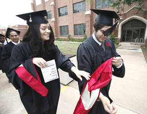 Photo - David Burkhart hurries to put on his regalia with help from Katie Lakin in a line of journalism graduates  heading into McCasland Field House for their convocation ceremony. PHOTOS BY STEVE SISNEY, THE OKLAHOMAN