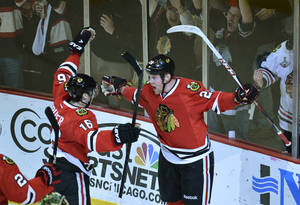 photo - Chicago Blackhawks center Marcus Kruger of Sweden, left, and left wing Bryan Bickell celebrate after Bickell scored during the first period of an NHL hockey game against the Minnesota Wild, Tuesday, March 5, 2013 in Chicago.  (AP Photo/Brian Kersey)