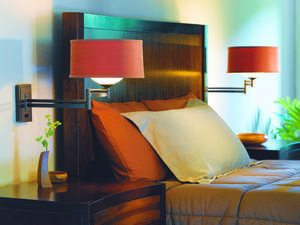 Photo - Wall-mounted fixtures with swing arms on either side of the bed let you shine light where you want it, and also leave more room on nightstands. Photo provided