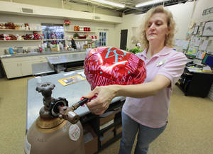 Photo - Georgianna Gleason fills a Valentine's Day balloon with helium at Trochta's Flowers & Greenhouses. <strong>David McDaniel - The Oklahoman</strong>