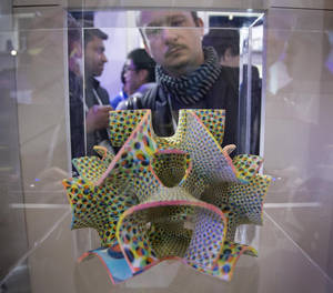 Photo - A trade show attendee examines a centerpiece confection made with a ChefJet Pro 3D food printer on display at the International Consumer Electronics Show, Thursday, Jan. 9, 2014, in Las Vegas. The candies are made with sugar, food coloring and a single flavor.  (AP Photo/Julie Jacobson)